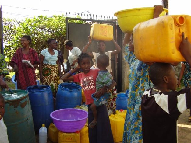 Familias del barrio recogiendo agua en el pozo de la escuela